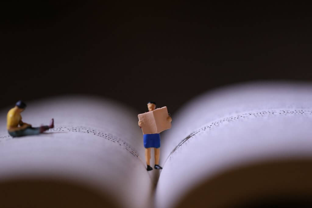 Lesende Miniaturen auf aufgeschlagenem Buch